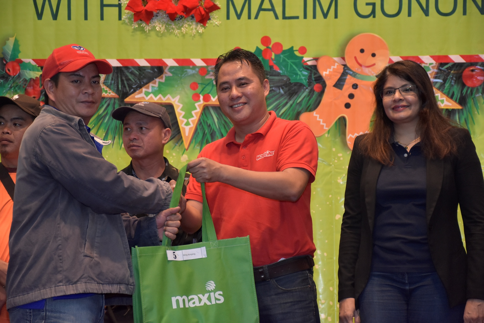 Maxis distributed school uniforms for the children of the mountain guides during the event. (From right - Mariam Bevi Batcha, Head of Corporate Affairs and Melvin Jeffrine Mojinun, Maxis Head of Sabah Region)